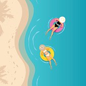 Two women swimming on the inflatable ring