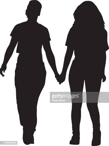 Two Young Women Walking Holding Hands Silhouette