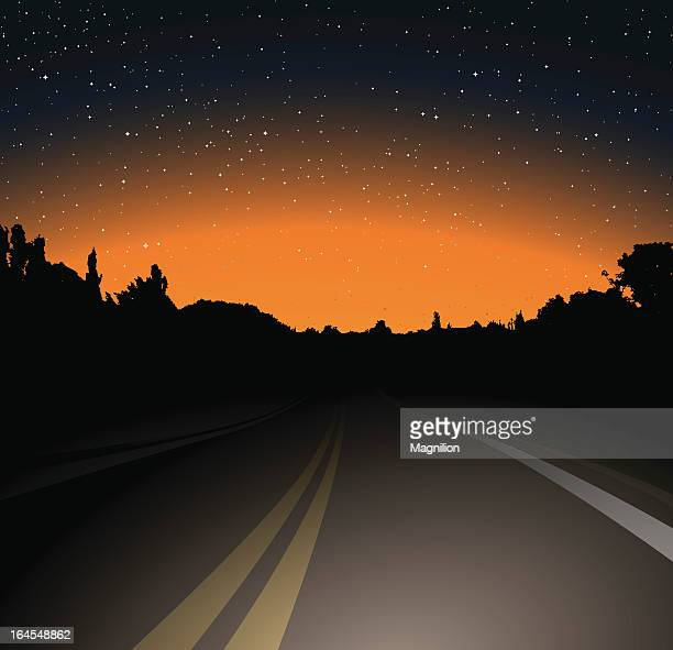 A unlit road on a dark night with building silhouette