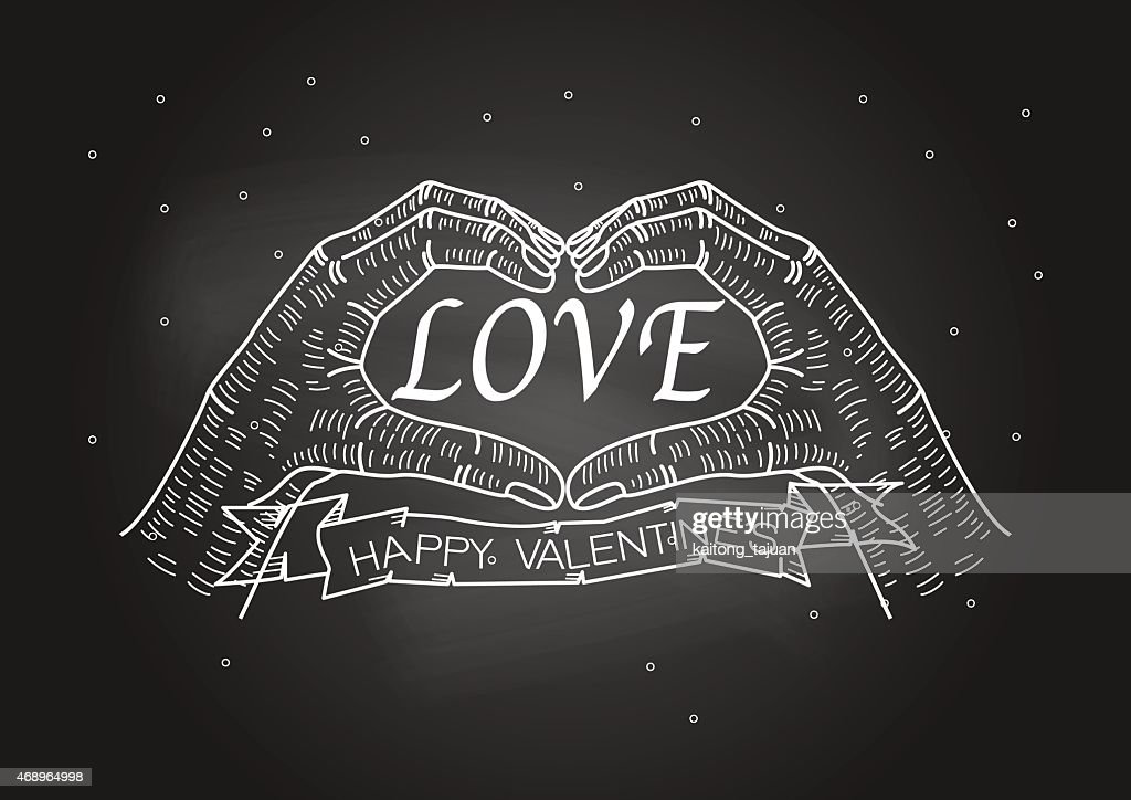 Valentine's Day, hand making heart sign on blackboard with chalk
