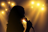 Vector black silhouette of female singer with yellow spotlights in the background