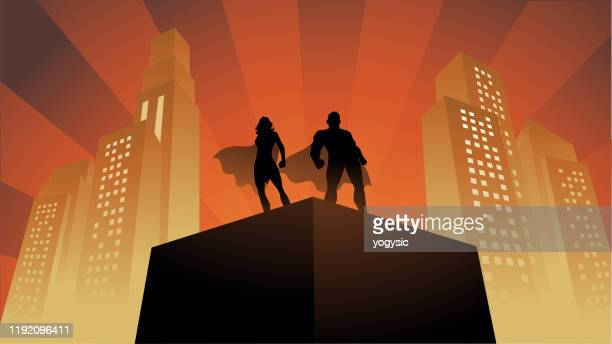 vector superhero couple silhouette on a rooftop with buildings in the background - superhero stock illustrations