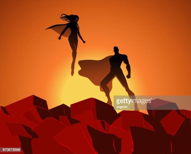 vector superhero couple silhouette on rocks - heroines stock illustrations