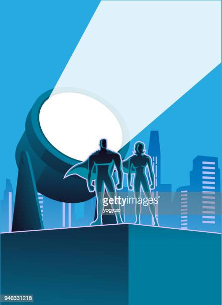 Vector superhero couple with searchlight and city skyline in the background