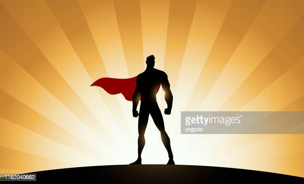 vector superhero silhouette with sunburst effect background - superhero stock illustrations