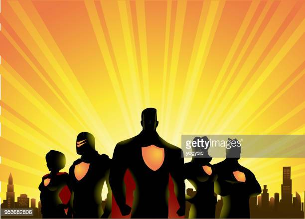vector superheroes team silhouette with city and sunrise background - superhero stock illustrations