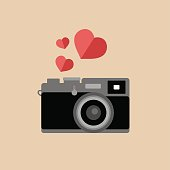 Vector vintage camera icon with hearts in trendy flat style.