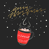 """Vector winter hand-drawn illustration of a knitted patterned red mug with hot cocoa and marshmallow and golden lettering """"Merry Christmas"""" on a black background."""