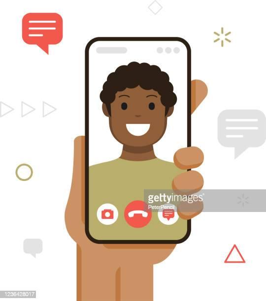 ilustraciones, imágenes clip art, dibujos animados e iconos de stock de concepto de videollamada. mano sosteniendo smartphone con el joven hombre afroamericano en la pantalla. ilustración vectorial del teléfono móvil en la mano. aislado sobre fondo blanco. plantilla - africano americano
