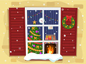 View of the cozy Christmas living room with a tree and fireplace through the window.