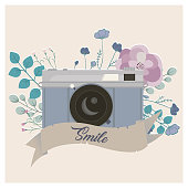 Vintage camera decorated with flowers and ribbon. Smile lettering. Vector illustration