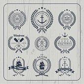 Vintage nautical wreath labels set on light wood background