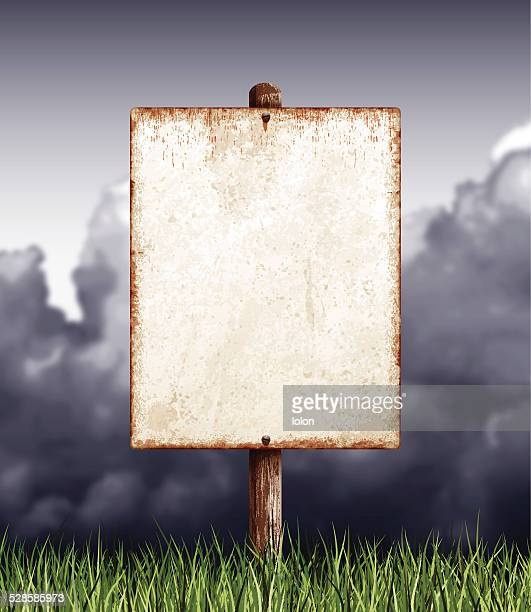 Weathered blank placard with wooden post, field and clouds