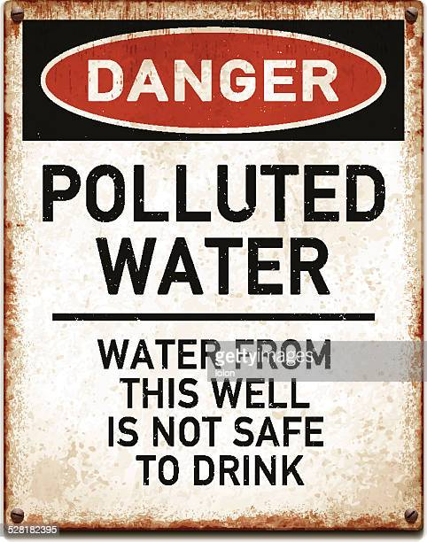 weathered metallic placard with danger polluted water text_vector - water pollution stock illustrations