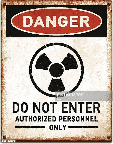 weathered metallic placard with danger radioactive trefoil symbol_vector - radioactive contamination stock illustrations