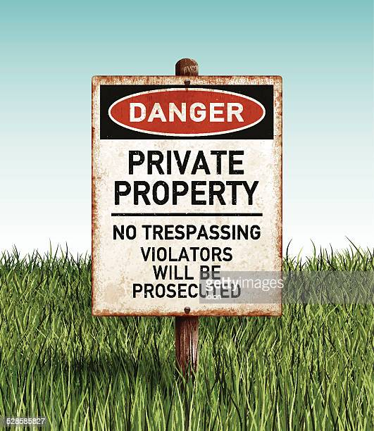 Weathered private property placard with wooden post and grass field