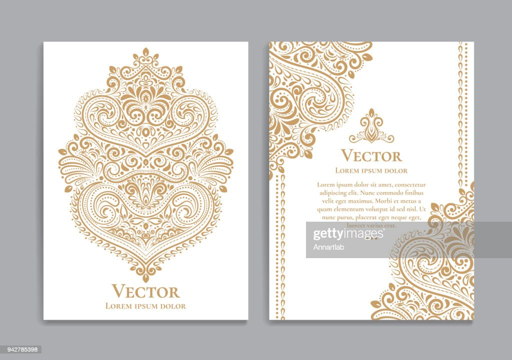 White and gold invitation cards with a luxurious vintage pattern.