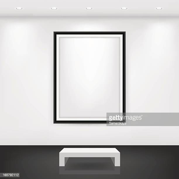 White bench in front of an empty black frame on a white wall