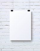 White vertical blank piece of paper on the white brick