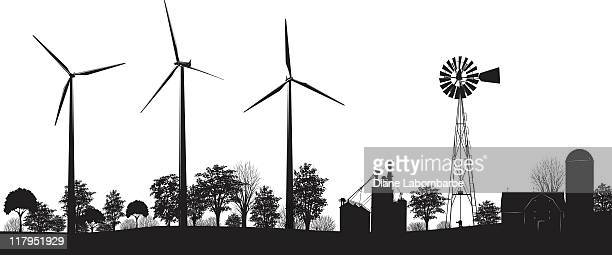 Wind Turbines on Farmland with trees and buildings black silhouette