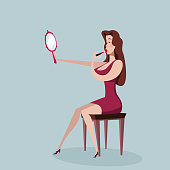 Woman applying lipstick looking at mirror in hand