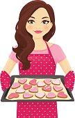 Woman baking heart shape cookies