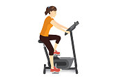 Woman doing exercise with stationary bicycle for firming her body.