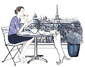 Woman having breakfast on a balcony in Paris
