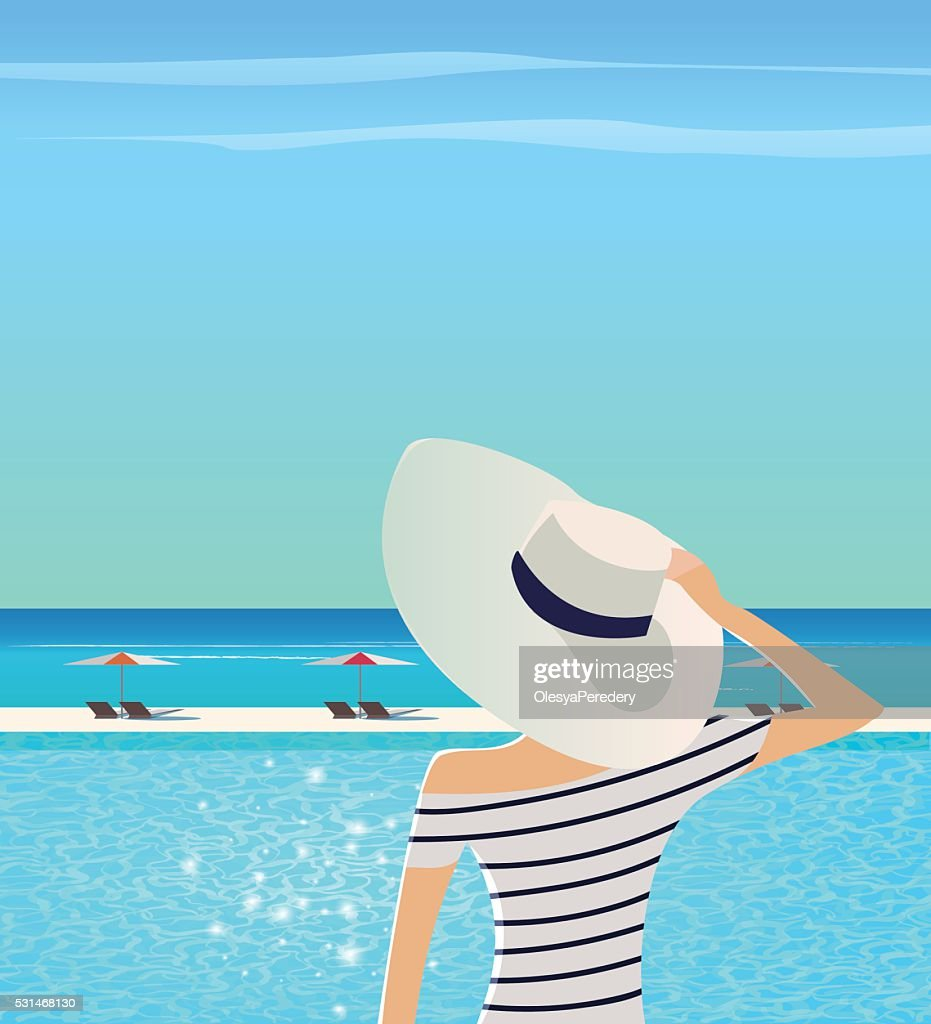Woman in wide-brimmed hat is admiring sea.