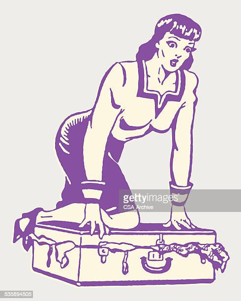 Woman ひざまずくにスーツケースに閉じた