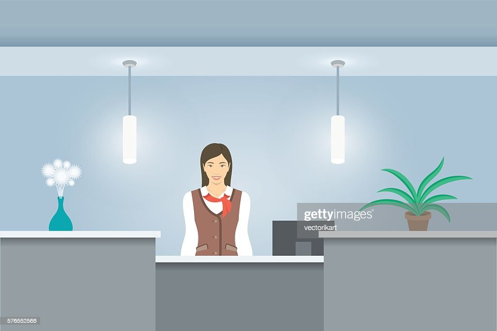 Woman receptionist in uniform stands at reception desk front view