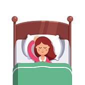 Woman sleeping peacefully smiling in her bed
