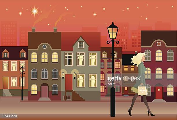 Woman Walking Down Street with Townhouses at Night