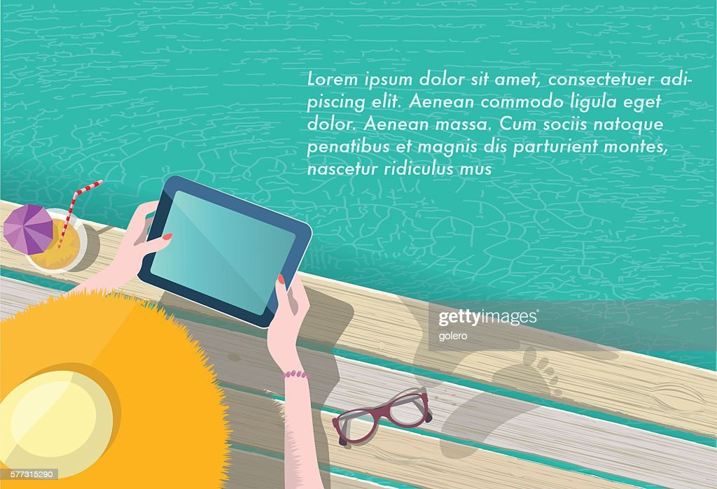 woman with summer hat reading on tablet at pool