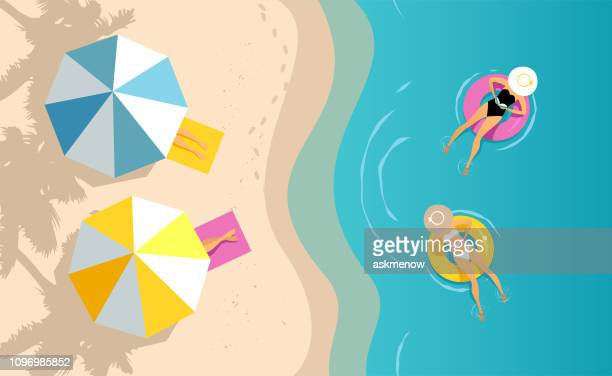 women swimming on the inflatable ring - water's edge stock illustrations