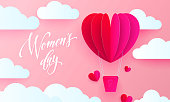 Women's day text on pink paper art heart balloon with gift box on white cloud pattern background. Vector 8 March card