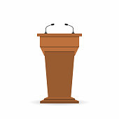 Wooden podium tribune stand rostrum with microphones. Back view from audiences side