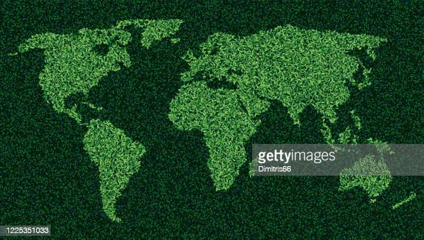 world map made form leaves and grass - earth day stock illustrations