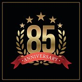 85 years golden anniversary icon, with star, red ribbon, and  laurel wreath isolated on black background, vector design