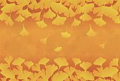 Yellow ginkgo leaves in orange brown background