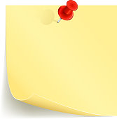 Yellow notepad pinned to the wall by red thumbtack