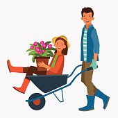 Young and smiling man pushing his laughing girlfriend in a wheelbarrow