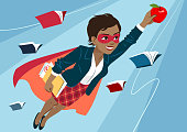 Young black woman in cape and mask flying through air in superhero pose, looking confident and happy, holding an apple and folder with papers, open books around. Teacher, student, education learning concept