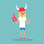 Young blond girl wearing horned hat and foam finger