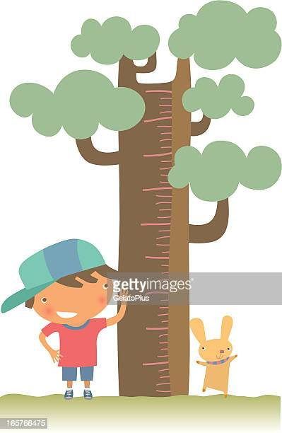 Young boy and pet checking their height against a tree