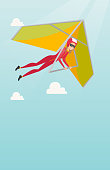 Young caucasian woman flying on hang-glider