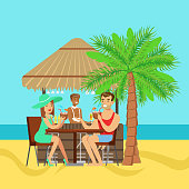 Young couple sitting at the cafe near the beach