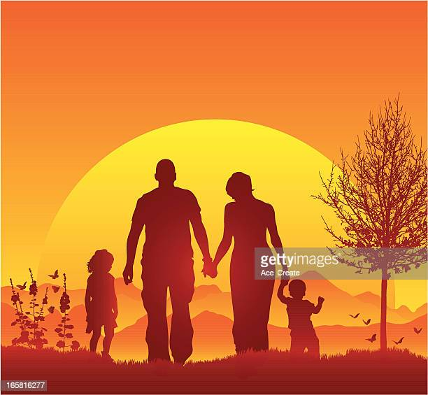 Young family walking in silhouette during a beautiful sunset
