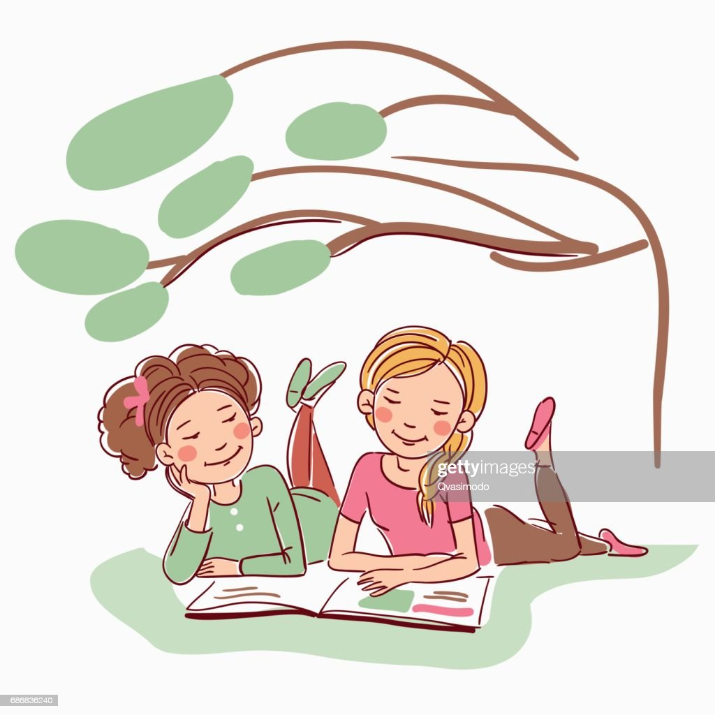 Young girls reading a book under the tree