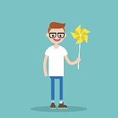 Young happy character holding a toy windmill / flat editable vector illustration, clip art